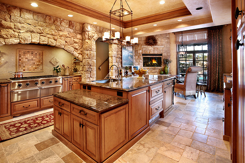 brick, carpet, curtains, fire, fireplace, granite, island, kitchen, lights, marble, sink, stove, table, wood
