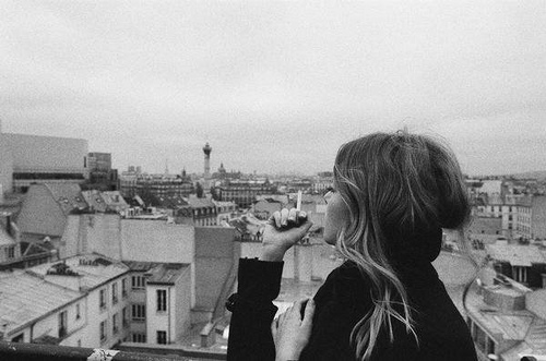 black, black and white, brunette, building, buildings, cigarette, city, coat, face, girl, hair, hands, looking, photography, pretty, sky, smoke, smoking, town, view, wind